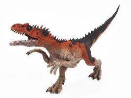 Saurophaganax dinosaur rubber toy isolated on white photo