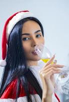 Asian woman wearing  Santa Claus hat Celebrate Christmas by drinking champagne happily photo
