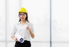 Retrato de una hermosa arquitecta con un casco amarillo en el trabajo y un documento en un sitio en construcción foto