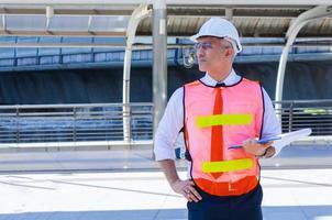 ingeniero sostiene una computadora portátil para supervisar el sitio de construcción de un edificio moderno los ingenieros usan cascos de seguridad blancos por seguridad foto