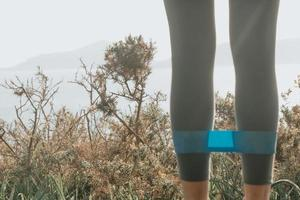 Woman doing exercises in the forest with a rubber band photo