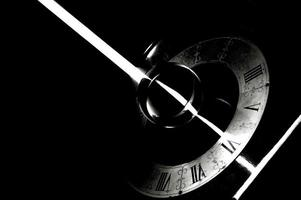 A vintage clock with a bright ray of light in black and white photo