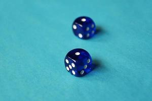 A vibrant monochromatic macro with depth of field about two blue glass gambling dice with two unlucky number one on blue background photo
