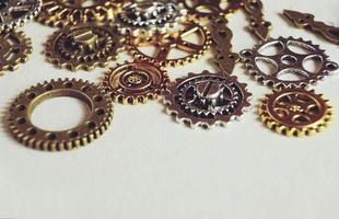 Una macro steampunk y antigua sobre maquinaria hecha de engranajes de bronce, plata y oro con fondo beige. foto