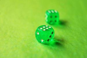 A vibrant monochromatic macro with depth of field about two green glass gambling dice with two lucky number six on green background photo