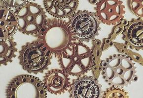 Un steampunk y una antigua macro plana sobre maquinaria hecha de engranajes de bronce, plata y oro con fondo beige. foto