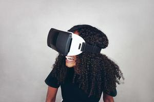 A beautiful young black woman with curly afro hair wears virtual reality VR headset and plays videogames while smiling in studio with grey background photo