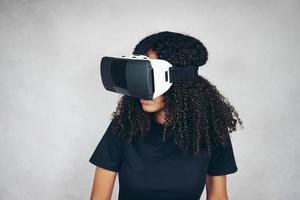 Una hermosa joven negra con cabello afro rizado usa auriculares de realidad virtual vr y juega videojuegos en estudio con fondo gris foto