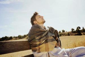 Cara lateral de un hombre joven con los ojos cerrados disfrutando en calma del sol de otoño de la mañana en un campo amarillo con la luz de fondo del cielo azul foto