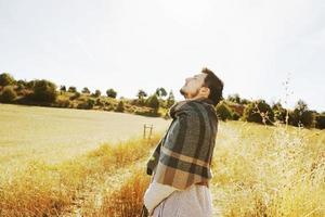Lado de un stand joven disfrutando en calma el sol de otoño de la mañana en un camino de un campo amarillo con la luz de fondo del cielo azul foto