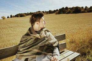 Cara lateral de un joven sentado con los ojos cerrados disfrutando en calma del sol de otoño de la mañana en un campo amarillo foto