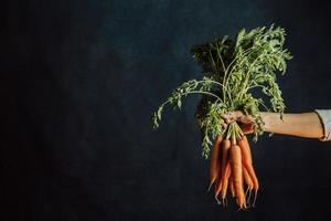 Hand grabbing a bunch of carrots photo