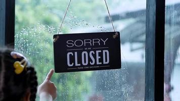 Un panneau ouvert accroché à la porte d'entrée du restaurant se balançant un jour de pluie video