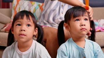 Cerca de la encantadora niña está mirando la televisión mientras su madre está peinando el cabello de su hija en la sala de estar video