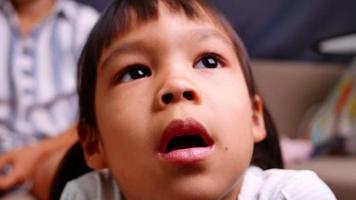 Close up portrait of little girl regarde des dessins animés à la télé à la maison dans le salon video