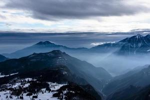 snow capped alpine peaks in the clouds five photo