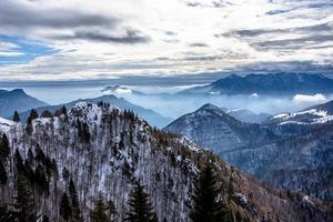 snow capped alpine peaks in the clouds photo