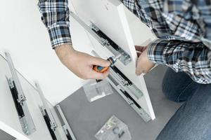 Hombre montando muebles con un destornillador foto