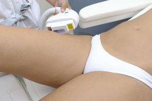 Cosmetology  Closeup Of Beautician Doing Laser Epilation Treatment On Beautiful Female Body Removing Hair On Silky Skin photo