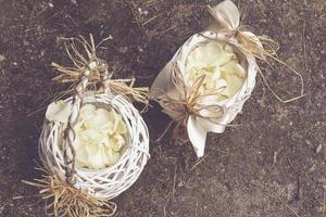 Wooden bouquet basket with white rose petals photo