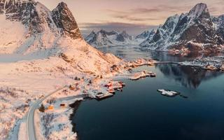 Aerial view of Scandinavian village on coastline in snowy valley at sunset photo