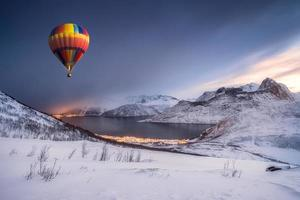 Hot air balloon flying on snow hill with fordgard town in winter photo