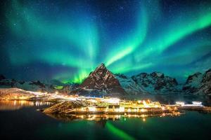 Aurora borealis over mountains in fishing village photo