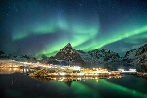 Aurora borealis over mountains in scandinavian village glowing photo