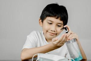 Closeup of a boy face washing his hands with alcohol gel photo