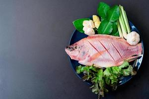 Top view of fresh fish and vegetables in ceramic dishes prepared for cooking with copy space photo