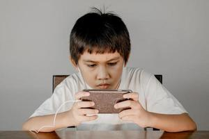 Closeup of a boy face wearing headphones and intending to play games on his smartphone photo