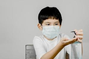 Closeup of a boy face wearing a sanitary napkin mask and washing his hands with alcohol gel photo