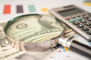 Magnifying glass and US dollar banknotes on graph photo