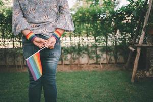 dama asiática sosteniendo la bandera de colores del arco iris símbolo del mes del orgullo lgbt celebrar anual en junio social de gays lesbianas bisexuales transgénero derechos humanos foto
