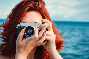 Female redhead person at ocean with camera photo
