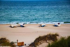 four boats in the sand and blue sea photo