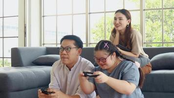 Asian family enjoy their holidays at home father and daughter play video games having fun