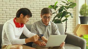 père et fils asiatiques utilisent leur carte de crédit pour les transactions en ligne video