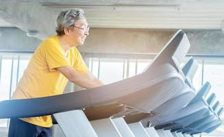 Asian elderly man exercising in the gym photo