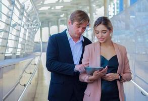 Business men and women talk about business market and hold laptops photo