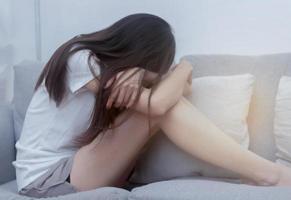una mujer enferma de depresión y tortura en su dormitorio foto
