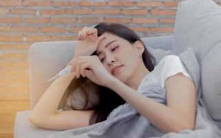 mujer asiática está enferma debido a una enfermedad y está sosteniendo un termómetro foto