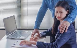 hermosas empleadas jóvenes son acosadas sexualmente por empleadores jóvenes de acoso sexual en la oficina al sostener la patada en el hombro retrato igualdad de género foto