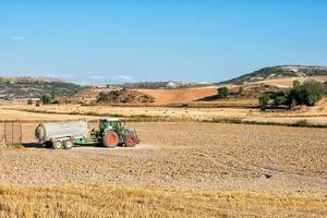 maquinaria agrícola trabajando la tierra en un día soleado foto