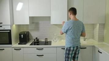 un uomo in pigiama che beve acqua al mattino in cucina video