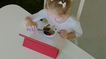 Little girl eats and plays using a tablet web surfing video