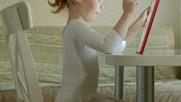 Cute little girl in white clothes sitting in the kitchen at the table and playing using a tablet, Web surfing, close up portrait video