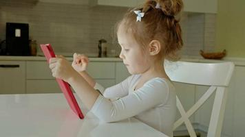 Cute little girl in white clothes sitting in the kitchen at the table and playing using a tablet, Web surfing video