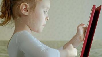menina bonitinha com roupas brancas, sentada na cozinha à mesa e brincando usando um tablet, navegar na web, close-up retrato video
