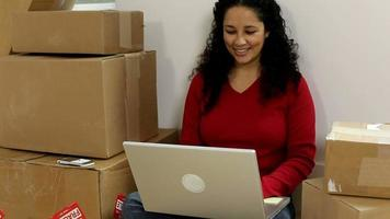 Woman sitting by unpacked boxes with laptop video